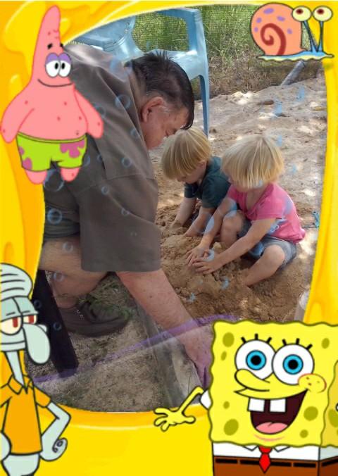 Oupa speel in die sand saam met die meisies